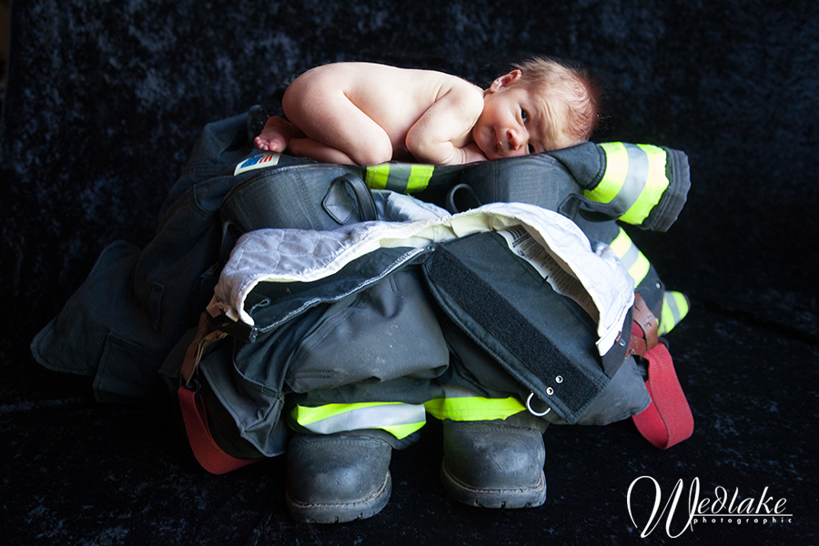 Newborn baby with firefighter gear